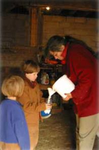 Donna and some young helpers prepare a bottle of milk for goat kids