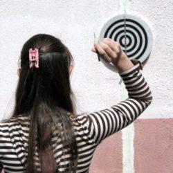 Girl throws dart
